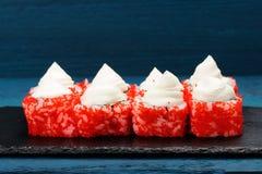 Hemlagad smaklig sushi med den röda tobikofiskromen och gräddost på blått Royaltyfria Bilder