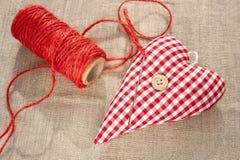 Hemlagad sydd röd bomullsförälskelsehjärta. Closeup. Royaltyfria Foton