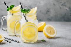Hemlagad uppfriskande sommarlemonaddrink med citronskivor och is i murarekrus royaltyfri bild