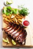 Hemlagade bakade köttstöd tjänade som med franska småfiskar, örter, limefrukt och ketchup på ett träbräde Lantlig stil royaltyfri bild
