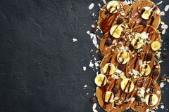 Hemlagade bananpannkakor med karamell, muttrar och chokladchiper T Royaltyfri Foto