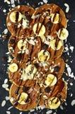 Hemlagade bananpannkakor med karamell, muttrar och chokladchiper T Arkivbild