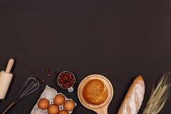 Hemlagade bröd eller bulle-, giffel- och bageriingredienser, mjöl, mandelmuttrar, hasselnötter, ägg på mörk bakgrund, bageribackg arkivbilder