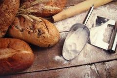 Hemlagade bröd med matlagningredskap Arkivbilder