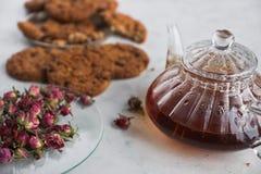 Hemlagade choklade kakor, kokkärl med svart te och rosor, garnering för tebjudning Fotografering för Bildbyråer