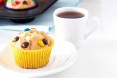 Hemlagade citronmuffin med den färgrika chokladgodisen i pappers- fall och kopp te Vit bakgrund Selektivt fokusera royaltyfri bild