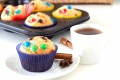 Hemlagade citronmuffin med den färgrika chokladgodisen i pappers- fall- och koppte Vit bakgrund Selektivt fokusera royaltyfri fotografi