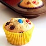 Hemlagade citronmuffin med den f?rgrika chokladgodisen i pappers- fall Vit bakgrund Selektivt fokusera fotografering för bildbyråer