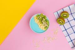 Hemlagade den sunda yoghurtkiwier och granola eller myslit bantar frukosten på en kulör bakgrund royaltyfria foton