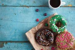 hemlagade donuts på pappers- och svart kaffe i en vit kopp Arkivfoto