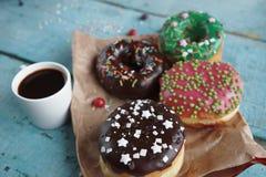 hemlagade donuts på pappers- och svart kaffe i en vit kopp Royaltyfria Bilder