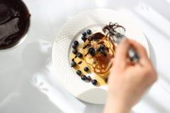 Hemlagade frukostpannkakor med bl?b?r och l?nnsirap arkivbild