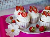 Hemlagade härliga muffin med mogna röda jordgubbar royaltyfria foton