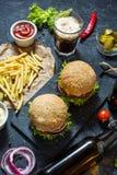 Hemlagade hamburgare med nötkött och stekt potatisar och exponeringsglas av kallt mörkt öl på stentabellen royaltyfria bilder