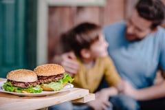 Hemlagade hamburgare på plattan med familjen bakom Arkivfoton