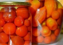 Hemlagade inlagda tomater i krus Arkivfoto
