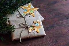 Hemlagade julgåvor i kraft papper med handgjorda etiketter och en julgran på träyttersida för mörk brunt Fotografering för Bildbyråer