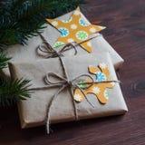 Hemlagade julgåvor i kraft papper med handgjorda etiketter och en julgran på träyttersida för mörk brunt Royaltyfria Foton