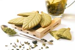Hemlagade kakor för mördegskaka för grönt te för matcha i form av gröna teblad på träställningen nära den nya koppen för grönt te royaltyfri fotografi