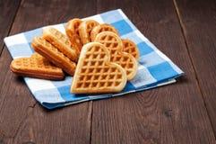Hemlagade kakor i form av hjärtor på en blå torkduk, brunt träskrivbord Royaltyfria Foton