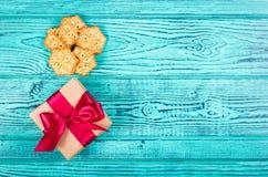 Hemlagade kakor i form av snöflingor och en gåvaask med en pilbåge Royaltyfri Bild