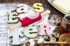 Hemlagade kakor i PÅSK för formbokstäver och ägg på gammal träbackgroun royaltyfri bild