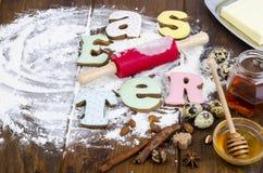 Hemlagade kakor i PÅSK för formbokstäver och ägg på gammal träbackgroun royaltyfria foton