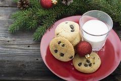 Hemlagade kakor med chokladdroppar för festmåltiden av Santa Claus i det nya året som omges av gran, förgrena sig, jul Arkivfoton