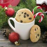 Hemlagade kakor med chokladdroppar för festmåltiden av Santa Claus i det nya året som omges av gran, förgrena sig, jul Arkivbilder