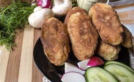Hemlagade kakor med potatisar, champinjoner Arkivfoto