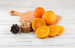 Hemlagade kakor och nya apelsiner på en vit trätabell Arkivfoto