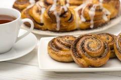 Hemlagade kanelbruna bullar och en kopp te på träbakgrunden Fotografering för Bildbyråer