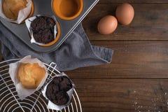 Hemlagade lagade mat muffin i en lantlig inställning med ingredienser som ska lagas mat på trätabellen med copyspace Arkivbild