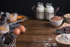 Hemlagade lagade mat muffin i en lantlig inställning med ingredienser som ska lagas mat på trätabellen med copyspace Royaltyfri Fotografi