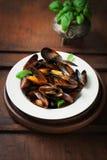 Hemlagade lagade mat musslor med vitlök, tomatsås, italienska örter, vitt vin och ny basilika i en platta royaltyfri fotografi