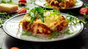 Hemlagade lasagner med finhackat nötkött bolognese och bechamelsås överträffade lös arugula, parmesanost Arkivfoton