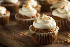Hemlagade morotmuffin med gräddostglasyr på kaka Arkivfoto