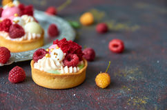 Hemlagade muffin med sötsakkräm och nya röda och gula hallon på ett grått oskarpt bakgrundsslut upp Royaltyfri Foto
