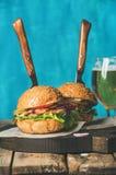 Hemlagade nötkötthamburgare med frasig bacon, lök, knipor, nya grönsaker Royaltyfri Foto