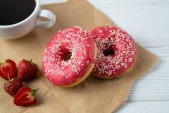 Hemlagade nya bakade donuts med jordgubberosa färgglasyr på kaka arkivbild