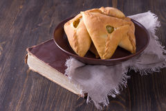 Hemlagade pajer med potatisar och lökar i en keramisk bunke på den gamla kokboken Royaltyfria Foton