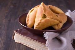 Hemlagade pajer med potatisar och lökar i en keramisk bunke på den gamla kokboken Royaltyfri Fotografi