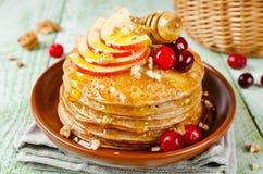 Hemlagade pannkakor med honung, äpplet, tranbär och muttrar Royaltyfri Bild
