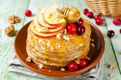 Hemlagade pannkakor med honung, äpplet, tranbär och muttrar Arkivbilder