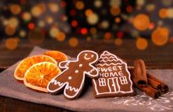 Hemlagade pepparkakakakor för jul på trätabellen, skivor av torra orange och kulöra ljus på bakgrund royaltyfria bilder