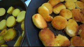 Hemlagade potatisar och fega klumpar steker i en stekpanna arkivfilmer