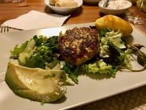 Hemlagade Salmon Meatballs Served med potatisar, avokadot och sallad i platta royaltyfri fotografi