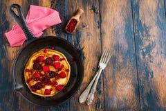 Hemlagade stekte pannkakor på en svart gjutjärnkastrull Är över bär, hallon, tranbär och björnbär Arkivbilder