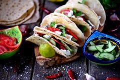 Hemlagade taco med köttfärs i tomatsås med nya tomater, gurkor, chili och mjuk ost Mexicansk mat royaltyfri bild
