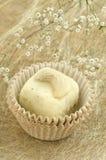 Hemlagade tryfflar för vit choklad med muttern på guld- bakgrund med blomman Royaltyfri Foto